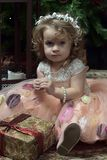 Wenig Mädchen in einem rosa Kleid, das auf dem Boden durch das Christma sitzt stockfoto