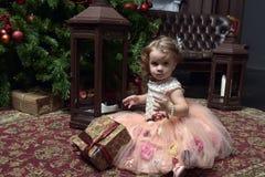 Wenig Mädchen in einem rosa Kleid, das auf dem Boden durch das Christma sitzt stockbild