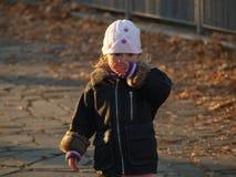 Wenig Mädchen in einem Stadtpark unter gefallenen gelben Blättern stockbild