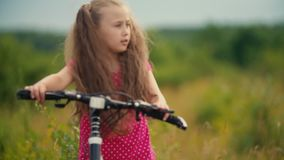 Wenig Mädchen in einer roten Klage, die ein Fahrrad reitet stock footage