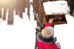 Wenig Mädchen fügt Nahrung der Zufuhr in der Winterparktiersorgfalt hinzu lizenzfreies stockbild