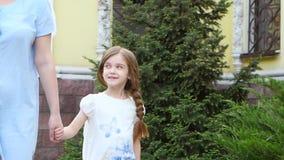 Wenig Mädchen hält die Hand ihrer Mutter und geht entlang die Straße stock video footage