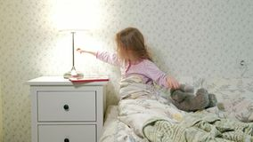 Wenig Mädchen im Bett, das auf Tablette spielt stock video footage