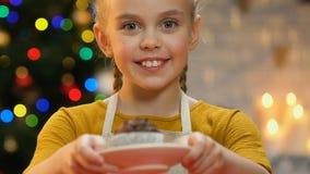 Wenig Mädchen im Schutzblechvertretungskleinen kuchen zur Kamera, stolz auf selbst gemachtes Gebäck stock footage