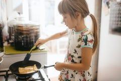 Wenig Mädchen kocht Pfannkuchen zum das Frühstück in der kleinen gemütlichen Küche lizenzfreies stockfoto