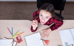 Wenig Mädchen lächelnd und glücklich mit Bleistift in ihrer Hand, die oben schaut lizenzfreies stockbild