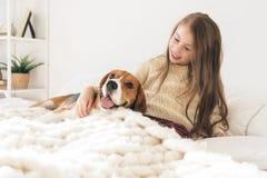 Wenig Mädchen mit dem Hund, der auf Bett und dem Lachen liegt stockfotos