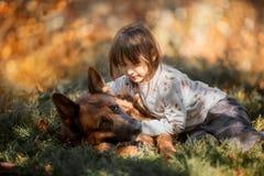 Wenig Mädchen mit dem Schäferhundhund im Freien lizenzfreie stockfotos