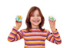 Wenig Mädchen mit den kleinen Kuchen verziert als Frühlingsblumen stockfoto