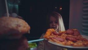 Wenig Mädchen nimmt Nahrung aus dem Kühlschrank heraus nachts stock footage