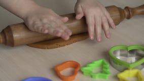 Wenig Mädchen rollt Teig mit Nudelholz auf weißer Tabelle für Weihnachtsplätzchen stock video footage