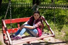Wenig Mädchen sitzt auf einem Schwingen im Park lizenzfreies stockfoto
