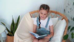 Wenig Mädchen sitzt im Lehnsessel, hält Tagebuch und sagt etwas, Zeitlupe stock video