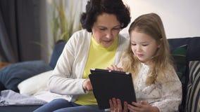 Wenig Mädchen stellt Cyberspiel Spaß der älteren Frau zum neuen auf Tablette dar stock footage