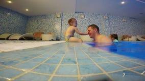 Wenig Mädchen umarmt ihren Vater im Pool stock footage