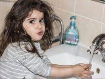 Wenig Mädchen wäscht ihre Hände im Badezimmer unter fließendem Wasser stockfotos