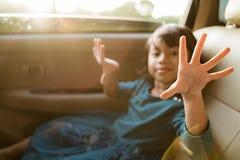 Wenig Mädchen, welches die Reise im Rücksitz genießt stockfoto