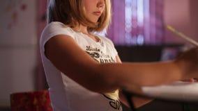 Wenig Mädchenblondine zeichnet einen Bleistift Gleitennockengesamtlänge Kamera bewegt sich nach links Nahaufnahme Weicher Fokus stock footage