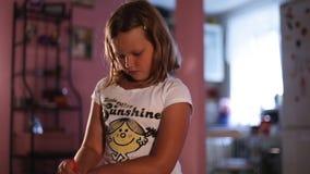 Wenig Mädchenblondine zeichnet einen orange Bleistift auf dem Hintergrund - unscharfe Küche stock video footage