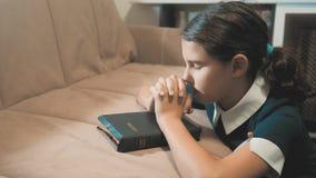 Wenig Mädchenjugendlicher, der in der Nacht betet Wenig Mädchenhandbeten heilige Bibel des kleinen Mädchens betet mit Bibel in ih stock footage