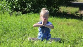 Wenig Mädchenpraxisyoga auf grünem Gras stock video footage