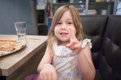Wenig Mädchensprechen und bewegliche Hände im Restaurant Lizenzfreies Stockfoto