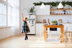Wenig Mädchentanzen auf Küche mit Weihnachtsdekorationen lizenzfreie stockfotografie