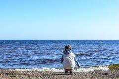 Wenig M?dchen auf einem einsamen Strand sitzt und sammelt Steine und Oberteile gegen den blauen Himmel und die sch?nen Wellen des stockbild