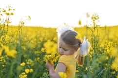 Wenig M?dchen romantisch auf dem Gebiet mit gelben Blumen lizenzfreie stockfotografie