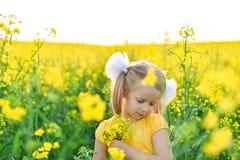 Wenig M?dchen romantisch auf dem Gebiet mit gelben Blumen lizenzfreie stockfotos