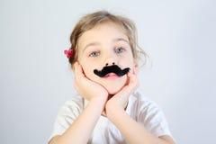 Wenig melancholisches Mädchen mit dem geklebten gefälschten Schnurrbart. Lizenzfreie Stockfotografie