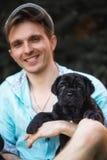 Wenig neapolitanischer Mastiffwelpe Schoßhund und sein lächelnder Eigentümer, die Spaß-Freien hat Park auf Hintergrund stockbild