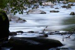 Wenig Nebenfluss mit Steinen stockbilder