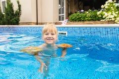Wenig nette blonde Mädchenschwimmen in einem Pool, tragende aufblasbare Ärmel Sie ist lächelnd und glücklich Lizenzfreies Stockfoto