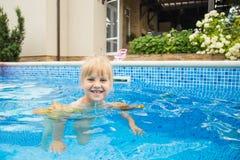 Wenig nette blonde Mädchenschwimmen in einem Pool, tragende aufblasbare Ärmel Sie ist lächelnd und glücklich Lizenzfreie Stockfotos