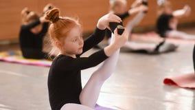 Wenig nette rothaarige M?dchenballerina f?hrt das Ausdehnen von ?bungen in der Ballettschule auf dem Hintergrund einer Gruppe von stock video