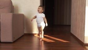 Wenig nettes Baby geht sicher auf den Boden und das Lächeln in der Zeitlupe stock video