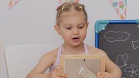 Wenig nettes Mädchen, das am Tisch im Kinderzimmer lächelt sitzt, die Fotos im Rahmen betrachtend stock video