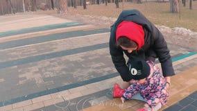 Wenig nettes Mädchen in einer bunten rosa Jacke zeichnet mit einer jungen Mutter mit Kreide auf einer Pflasterung nahe dem Spielp stock video