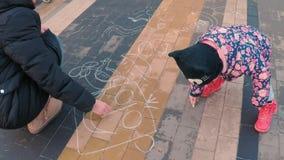 Wenig nettes Mädchen in einer bunten rosa Jacke zeichnet mit einer jungen Mutter mit Kreide auf einer Pflasterung nahe dem Spielp stock footage
