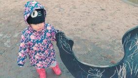 Wenig nettes Mädchen in einer bunten rosa Jacke zeichnet mit Kreide auf einer Tafel in Form eines Dinosauriers auf der Kinder stock video