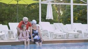Wenig nettes Mädchen mit den Zöpfen und reifer Frau, die am Rand des Pools mit ihren Füßen im Wasser sitzen stock video