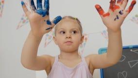 Wenig nettes M?dchen, das am Tisch im Kinderzimmer betrachtet seine H?nde, befleckt mit heller Farbe sitzt stock footage