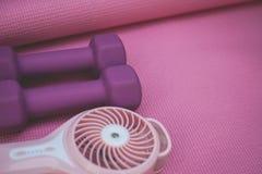 Wenig purpurrote Gewichte und ein tragbarer Fan stockbilder