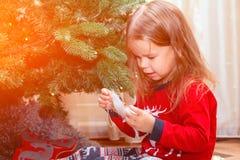 Wenig reizend Mädchen in den Pyjamas hilft ihren Eltern, den Weihnachtsbaum früh zu verzieren morgens, überprüft das Spielzeug stockfotos
