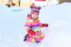 Wenig reizende 2 Jahre Mädchen spielt mit dem Schnee, der in der Winterzeit im Freien ist Lizenzfreie Stockfotografie