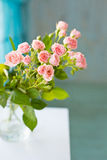 Wenig rosafarbene Blumen auf einem weißen Holztisch Lizenzfreie Stockfotos