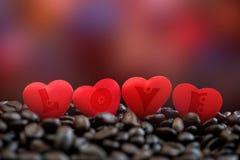 Wenig rote Satinherzen mit Buchstaben auf Kaffeebohnen, Valentinsgrußtag oder dem Hochzeitstagfeiern Stockbild