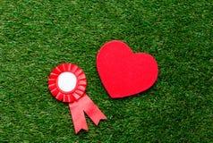 Wenig roter Siegerpreis und -herz formen Geschenk auf grünem Sommer gra Lizenzfreies Stockbild