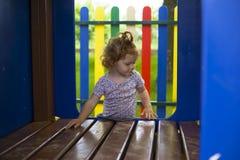 Wenig Rothaarigemädchen versucht, ein Holzhaus auf dem Spielplatz zu klettern stockbilder